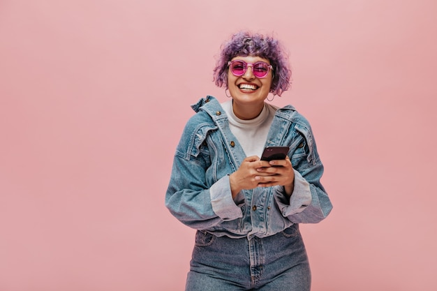 Leuke volwassen dame met helder kapsel in zonnebril lacht. glimlachende vrouw met de telefoon van de krullend haarholding.