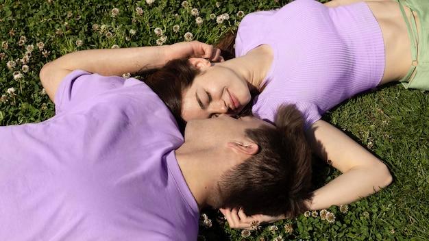 Leuke vriend en vriendin die op gras liggen