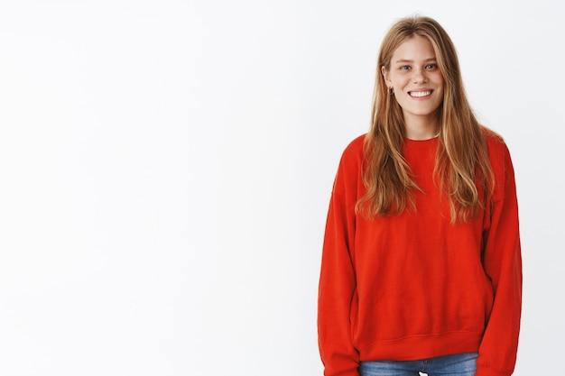 Leuke vriendelijk ogende gelukkige jonge fitte vrouw met schattige sproeten en lang kapsel in rode warme trui die breed glimlacht, ontspannen en zorgeloos poseren met zachte uitgaande uitdrukking over witte muur