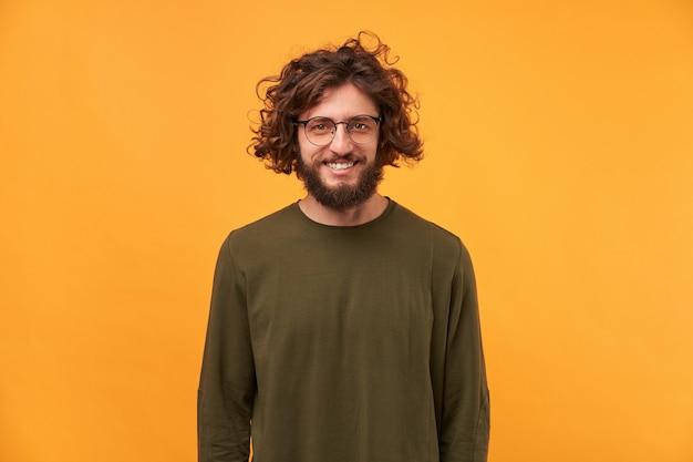 Leuke vriendelijke bebaarde man in glazen met krullend haar glimlachend kijkt gelukkig geïsoleerd op gele muur. een goede vriend kwam op bezoek, een aardige vent.