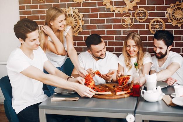 Leuke vrienden in een koffie die een pizza eatting