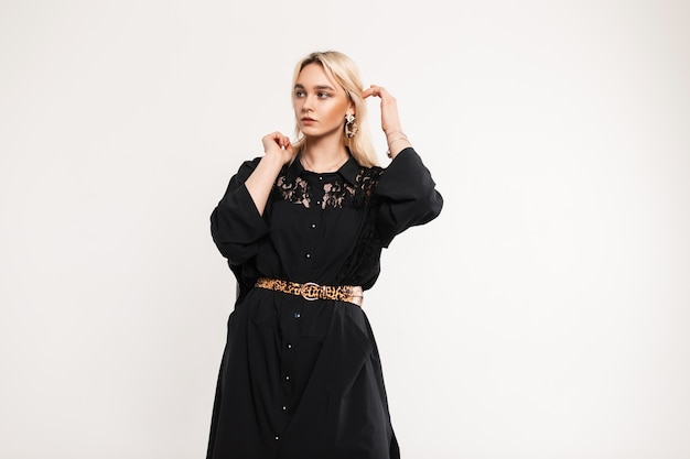 Leuke vrij aantrekkelijke elegante vrouw mannequin in modieuze lange zwarte jurk met kant poseren binnenshuis. stijlvol blond meisje in vintage kleding staat in de buurt van witte muur. aardige dame.