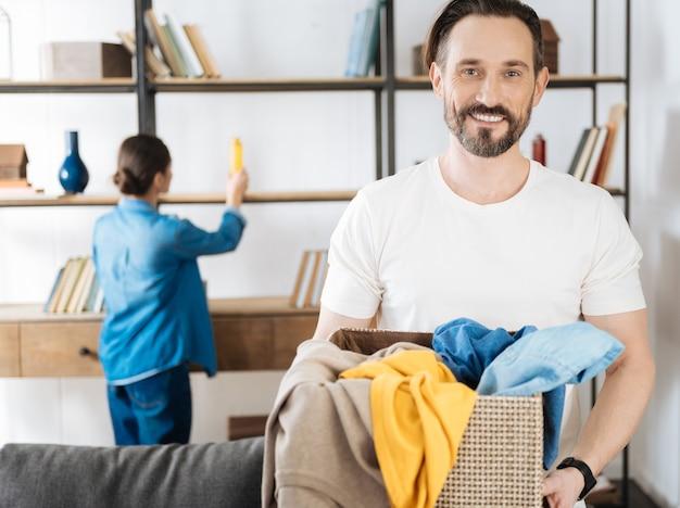 Leuke vrij optimistische echtgenoot die zich op de vage achtergrond bevindt terwijl hij direct kijkt en mand met kleren neemt