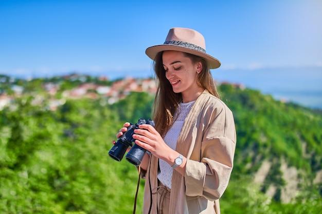 Leuke, vrolijke glimlachende jonge meisjesreiziger die hoed met verrekijker draagt tijdens vakantiereis op een heldere zonnige dag a
