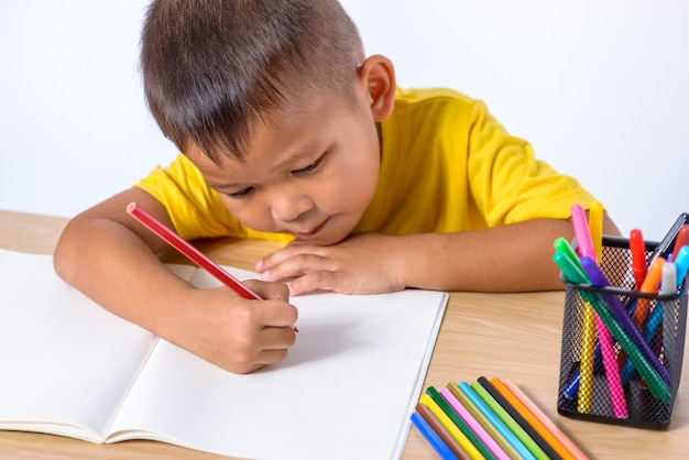 Leuke vrolijke kindtekening die kleurenpotlood gebruiken terwijl het zitten bij lijst op wit wordt geïsoleerd dat