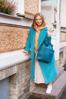 Leuke vrolijke vrouw in een blauwe jas en oranje trui met een tas in haar hand loopt op een lentedag door de stad