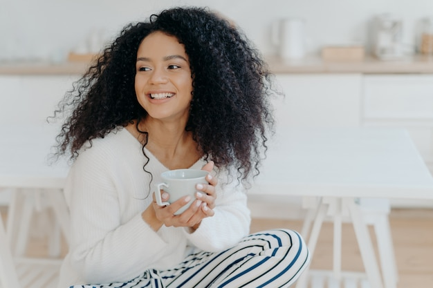Leuke vrolijke vrouw met borstelig krullend haar kijkt weg met een glimlach, houdt een mok koffie, draagt casual kleding