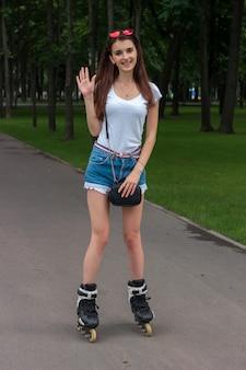 Leuke vrolijke vrouw staat op de rolarm zwaaien en glimlachen