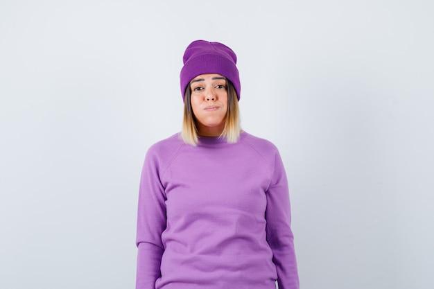 Leuke vrouw blaast wangen in trui, muts en kijkt verbaasd, vooraanzicht.