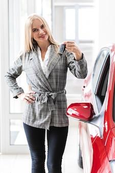 Leuke vrouw die bij sleutels van auto toont en de camera bekijkt