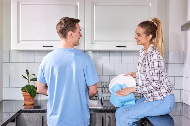 Leuke vrouw die de vaat afveegt terwijl haar man in de keuken wast, in vrijetijdskleding, praat, glimlacht, geniet van schoonmaken in het weekend. actieve vriendelijke familie thuis