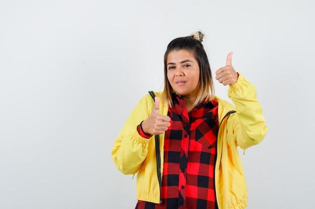 Leuke vrouw die dubbele duimen in shirt, jas toont en er zelfverzekerd uitziet, vooraanzicht.