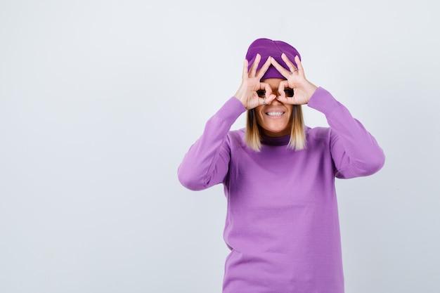 Leuke vrouw die een brilgebaar in trui, muts toont en er gelukkig uitziet, vooraanzicht.