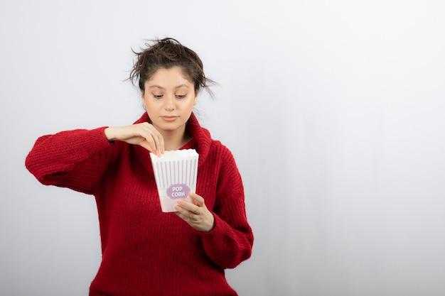 Leuke vrouw die een emmer met popcorn onderzoekt.
