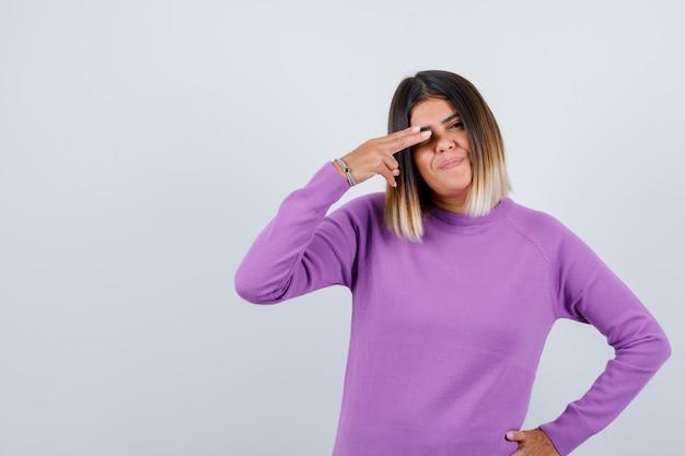 Leuke vrouw die een vingerpistool op het oog maakt in een paarse trui en er zelfverzekerd uitziet, vooraanzicht.