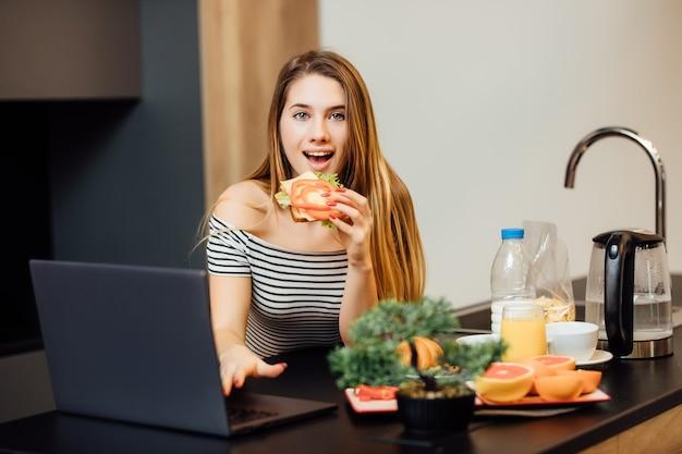 Leuke vrouw die gezond ontbijt terwijl ze een heerlijke sandwich eet en telefoon gebruikt in de keuken