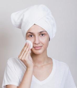 Leuke vrouw die haar gezicht schoonmaakt