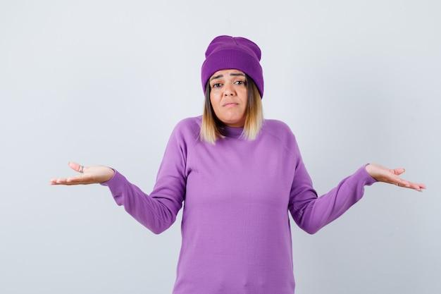Leuke vrouw die hulpeloos gebaar in trui, muts toont en verward kijkt, vooraanzicht.