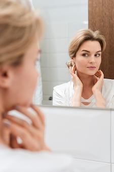 Leuke vrouw die in de spiegel kijkt
