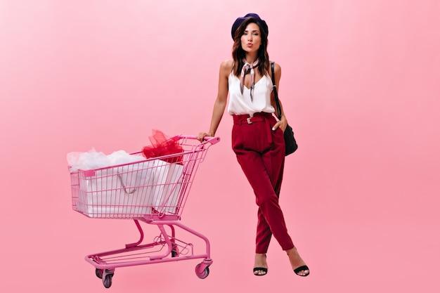 Leuke vrouw die in rode broek boodschappenwagentje op roze achtergrond houdt. meisje in een rode broek en witte blouse met sjaal om haar nek blaast kus in baret.