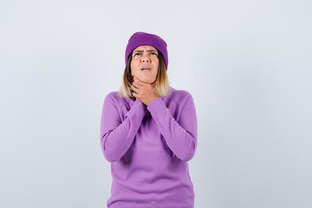 Leuke vrouw die lijdt aan keelpijn in trui, muts en er ziek uitziet. vooraanzicht.