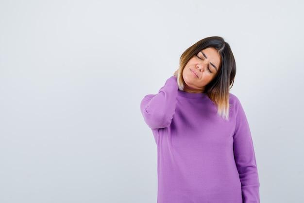 Leuke vrouw die nekpijn voelt in paarse trui en er moe uitziet, vooraanzicht.