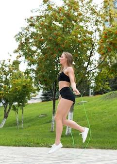 Leuke vrouw die op het touwtjespringen springt