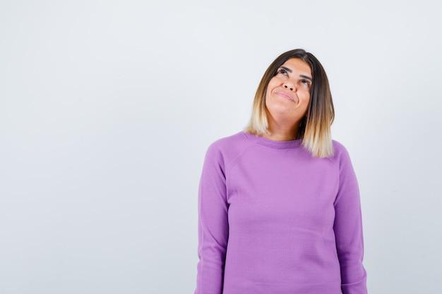 Leuke vrouw die opkijkt in paarse trui en er dromerig uitziet, vooraanzicht.