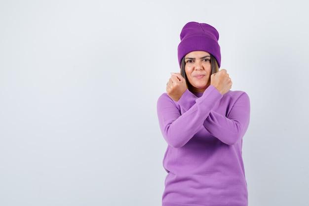 Leuke vrouw die protestgebaar in trui, muts toont en er zelfverzekerd uitziet. vooraanzicht.