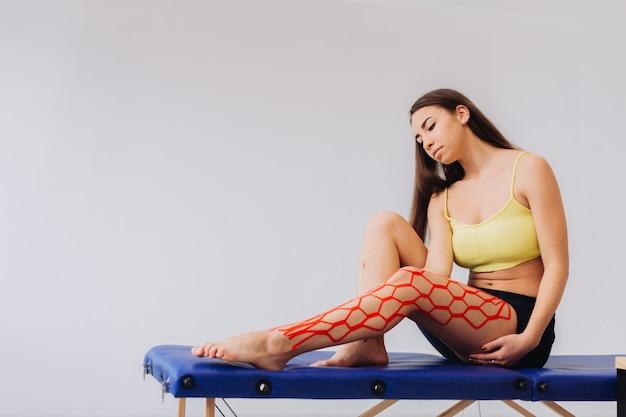 Leuke vrouw die rekbare kinesioband op haar knie en been plaatst.