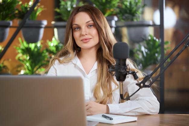 Leuke vrouw die voor online communiceren door laptop voorbereidingen treft