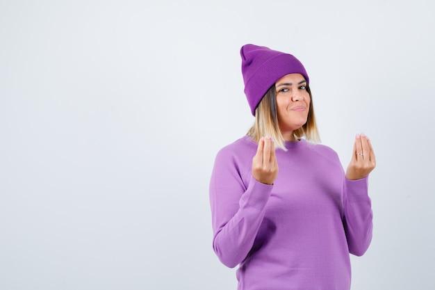 Leuke vrouw doet italiaans gebaar in trui, muts en ziet er vrolijk uit, vooraanzicht.