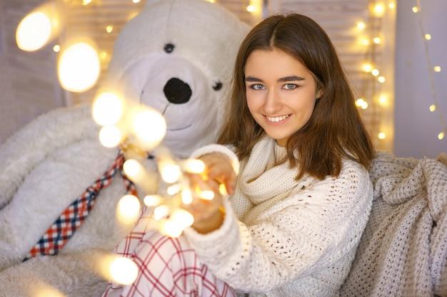 Leuke vrouw het glimlachen kerstmisstemming, heldere bokeh