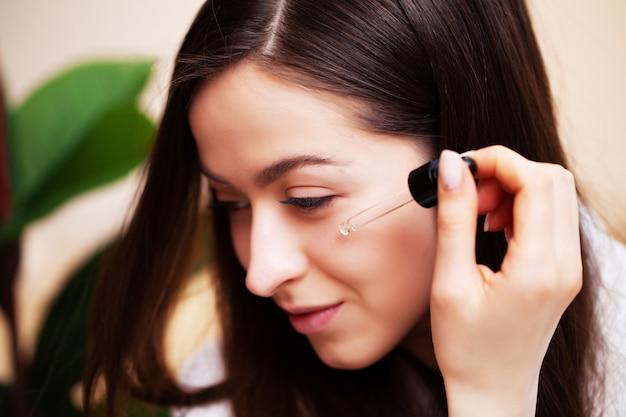 Leuke vrouw in badkamer doen cosmetische procedure voor gezichtshuid zorg
