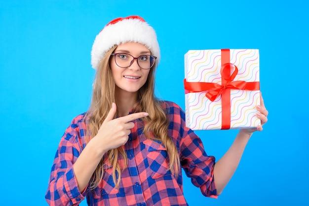 Leuke vrouw in glazen en kerstmuts wijzend op de geschenkdoos in haar hand