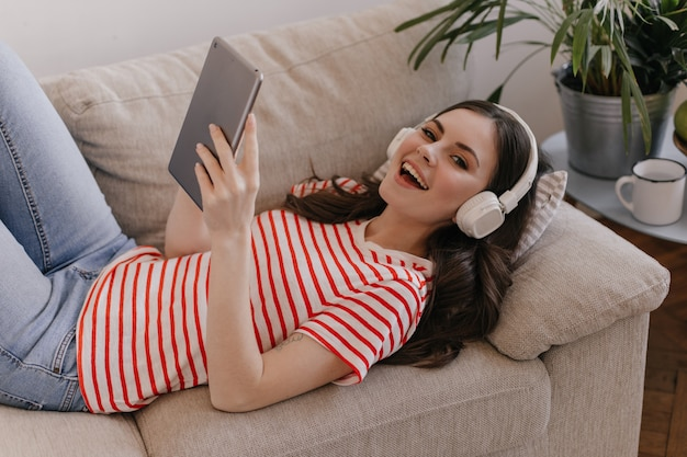 Leuke vrouw in nieuwe witte koptelefoon rust op zachte bank en plezier
