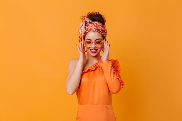 Leuke vrouw in oranje glazen, zijden jurk en hoofdband lacht op oranje ruimte.