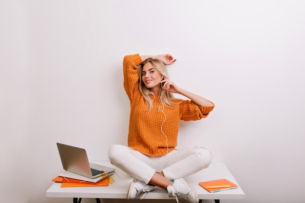 Leuke vrouw in oversized gebreid overhemd poseren met glimlach in haar gezellige kantoor