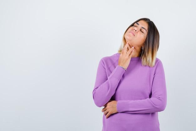 Leuke vrouw in paarse trui die de huid in de nek aanraakt, de ogen dicht houdt en er ontspannen uitziet, vooraanzicht.