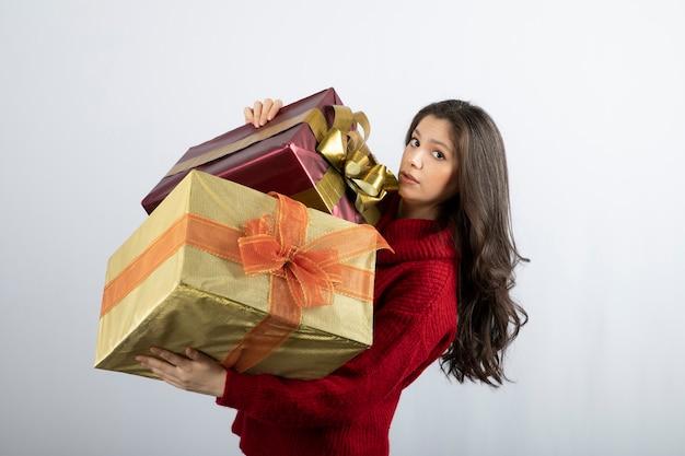 Leuke vrouw in rode trui met kerstcadeautjes.