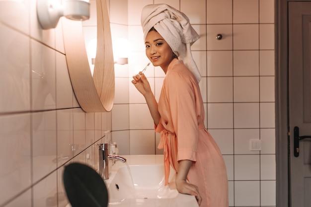 Leuke vrouw in roze gewaad reinigt tanden en kijkt naar voren tegen muur van badkamerspiegel