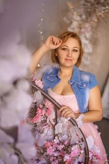 Leuke vrouw in roze jurk poseren tegen mooie bloemen