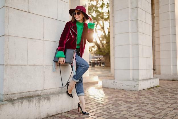 Leuke vrouw in trendy outfit in herfststijl die op straat loopt