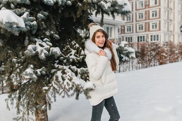 Leuke vrouw in trendy witte jas plezier tijdens winter fotoshoot en lachen. buiten foto van prachtige brunette dame draagt grappige hoed in koude zonnige dag.