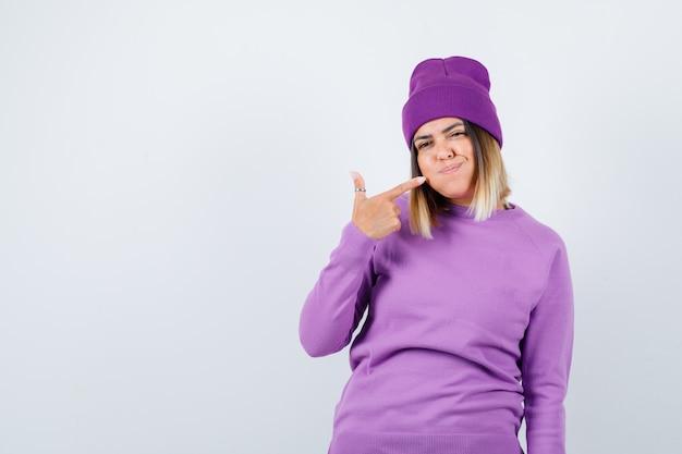 Leuke vrouw in trui, muts die naar haar mond wijst, wang blaast en er speels uitziet, vooraanzicht.
