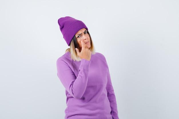 Leuke vrouw in trui, muts wijzend op haar ooglid en boos kijken, vooraanzicht.