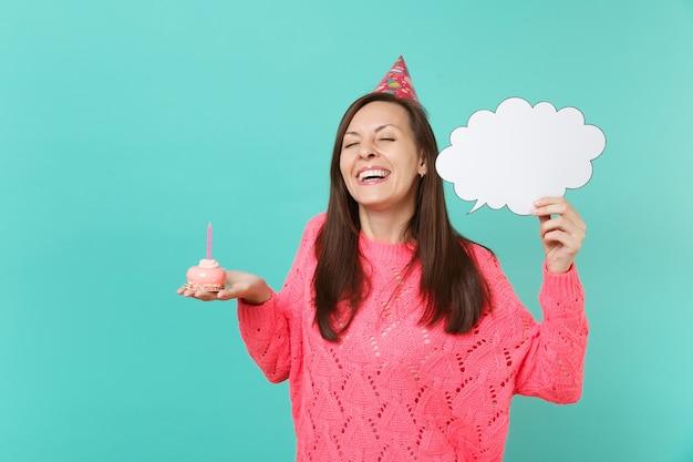 Leuke vrouw in verjaardagshoed met gesloten ogen houdt cake met kaars leeg leeg zeg wolk tekstballon voor promotionele inhoud geïsoleerd op blauwe achtergrond. mensen levensstijl concept. bespotten kopie ruimte.