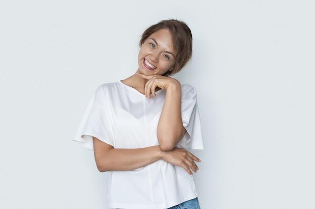 Leuke vrouw in wit t-shirt aanraken van haar kin lacht op een witte muur vol emoties