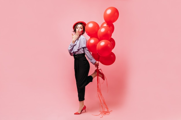Leuke vrouw in zwarte modieuze broek, blouse en heldere baret blaast kus, heft koket haar been op en houdt ballonnen vast op roze achtergrond.
