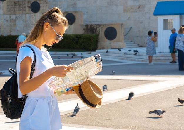 Leuke vrouw kijkt naar de kaart in de straat